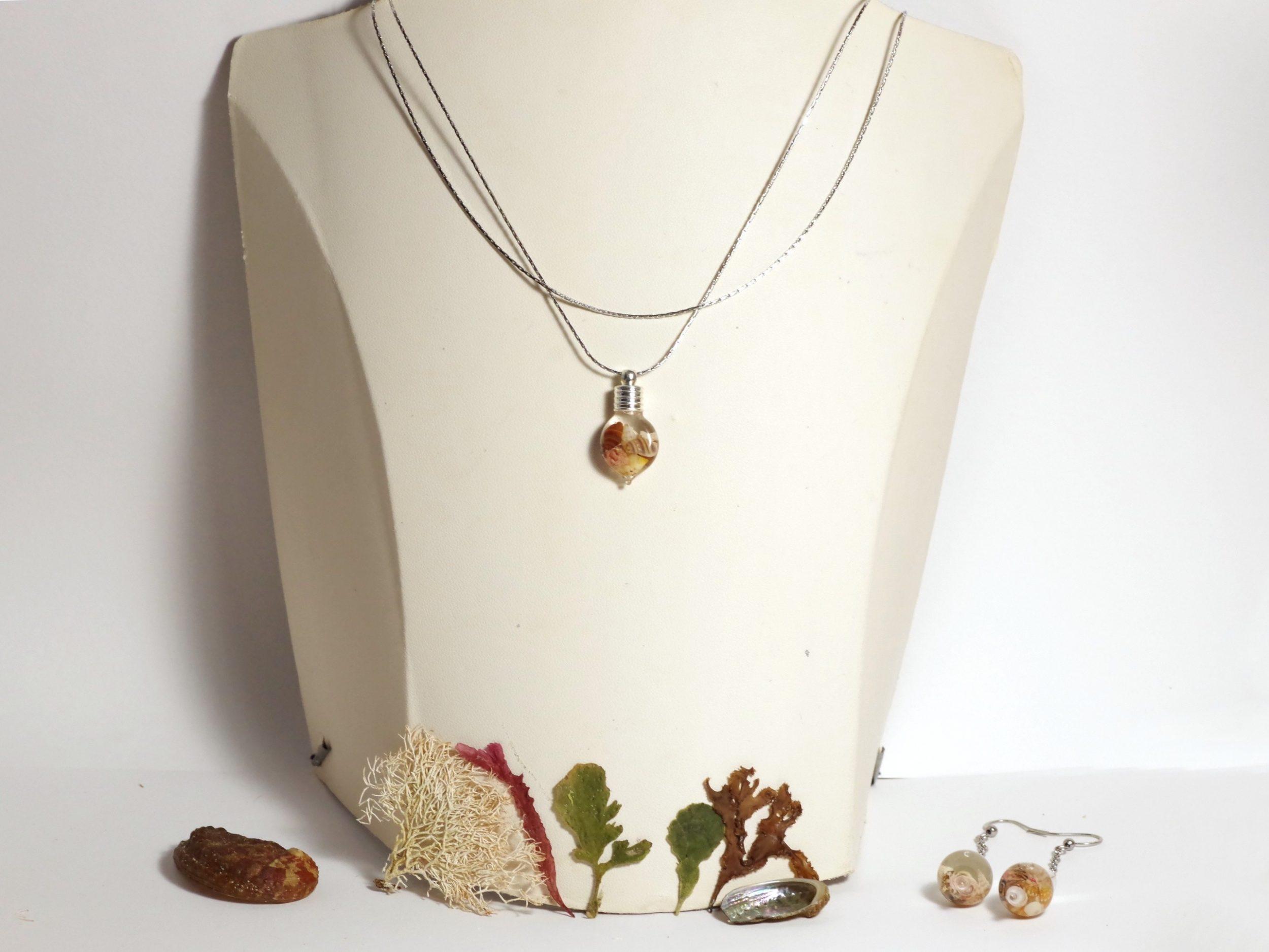 collier à deux chaînes, l'une d'elle porte un petit pendentif de verre : une fiole de macrocoquillage, les petits coquillages dans la fiole sont de couleurs variées à dominante brune