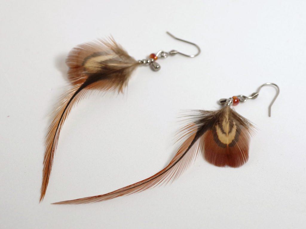 boucles d'oreilles en plumes : une fine plume marron et une plus petite aux graphismes marron et beige