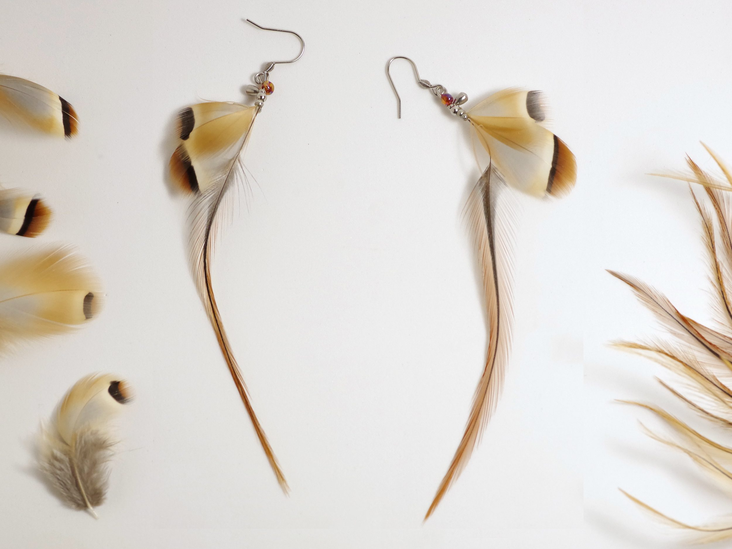 boucles d'oreilles aux longues et fines plumes marron associées à des pettes plumes grises et marron.