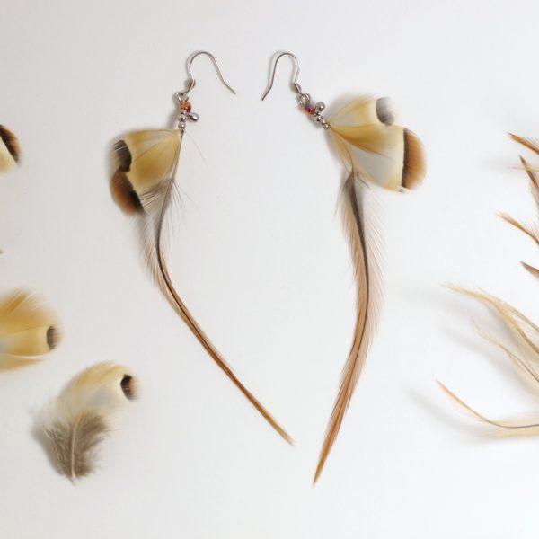 boucles d'oreilles aux longues et fines plumes marron associées à des petites plumes grises et marron.