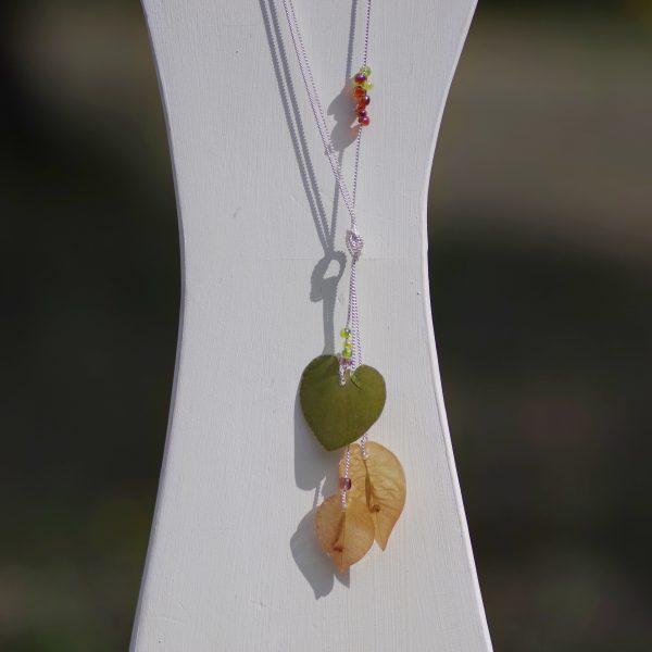 collier mi-long avec trois fines chaînes argentées nouées, portant 3 pendentifs végétaux vert et beige-rosé
