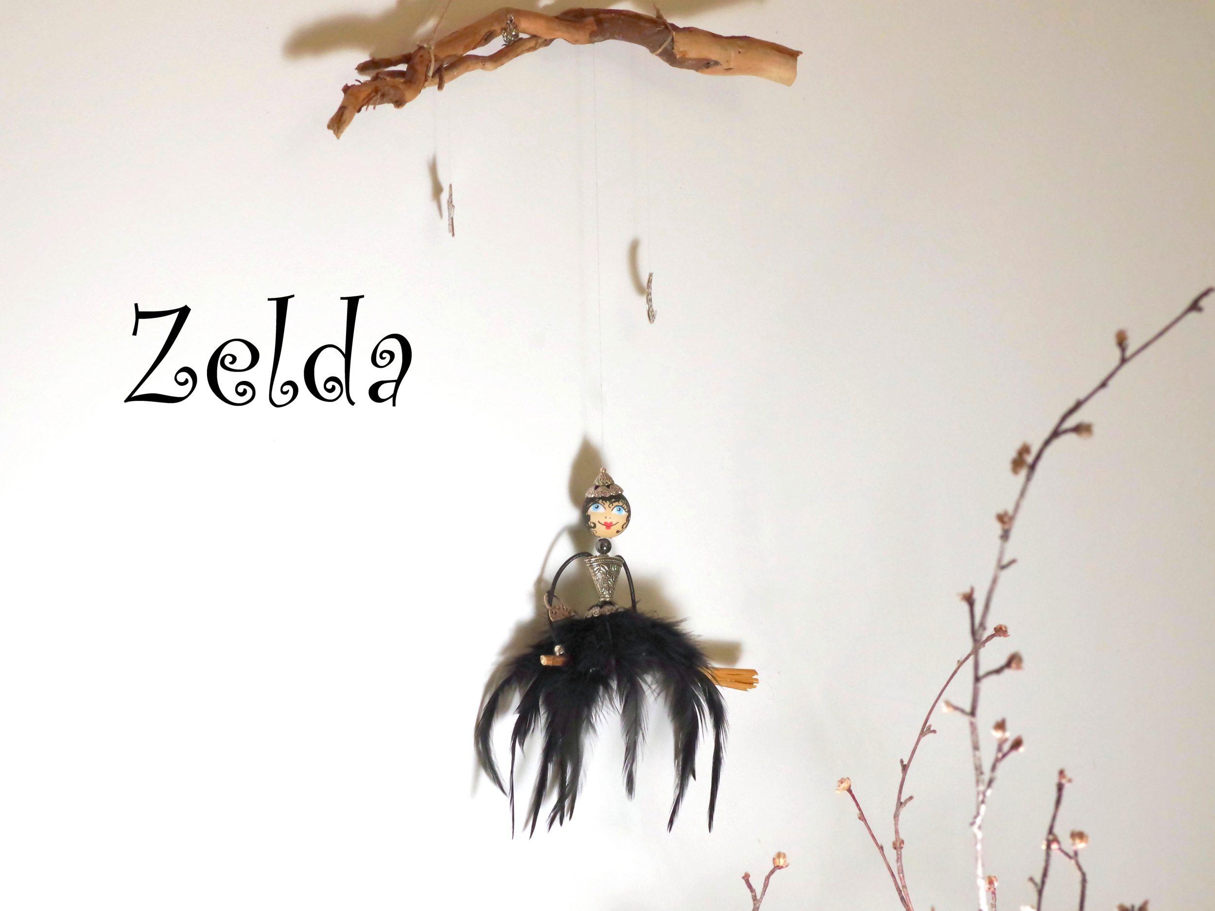 mobile gentille sorcière, sorcière à jupe de plumes noires sur un balai, lune, étoile et petit chat, le tout suspendu à un bois flotté
